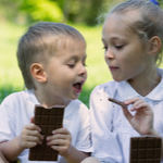 2 kids eating chocolate